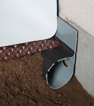 Closeup of a crawl space drainage system installed in Somerville