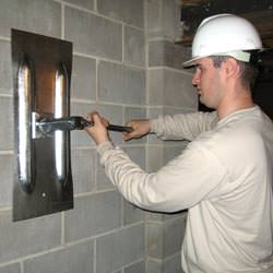 a contractor installing a foundation wall anchor in Tupelo