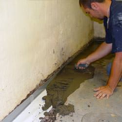 A basement waterproofer installing a perimeter drain system in Millington