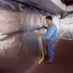 Installation of a radiant heat and vapor barrier on a basement wall in Eads